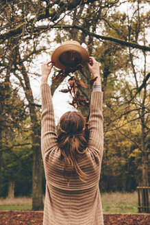 Back view of young woman dropping dried leaves on her head from a hat at park - CHAF000208