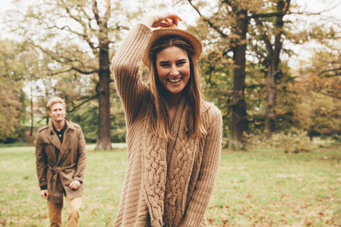 Portrait of young woman with hat in autumnal park with boyfriend in the background - CHAF000210