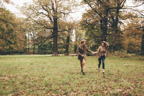 Young couple in love holding hands and running in an autumnal park - CHAF000212