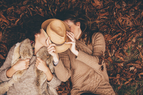 Two female friends lying side by side on autumn leaves in an park hyding behind a hat - CHAF000215