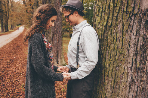 Young couple in love holding hands in an autumnal park - CHAF000221