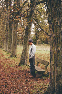 Young man standing in front of a bench in autumnal park - CHAF000223