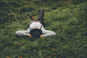 Young man lying on a meadow with hands behind his head - CHAF000228