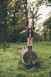 Little girl wearing cap standing with outstretched arms on a tree trunk in autumnal park - CHAF000237