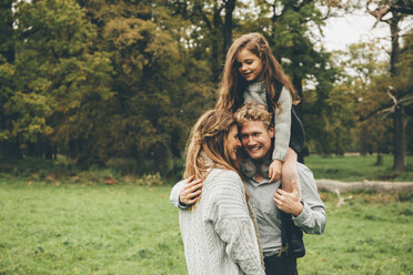Young couple with little girl on her father's shoulders at autumnal park - CHAF000242