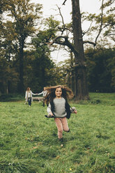 Little girl running on a meadow in a park while her parents standing in the background - CHAF000244