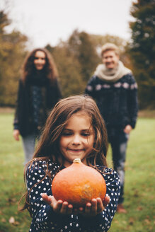 Portrait of smiling little girl showing Hokkaido pumpkin while her parents standing in background - CHAF000249