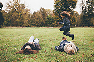 Young parents lying on a meadow while little girl jumping over them in a park - CHAF000250