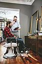 Barber with customer using digital tablet - MADF000333