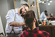 Barber brushing beard of a customer - MADF000337