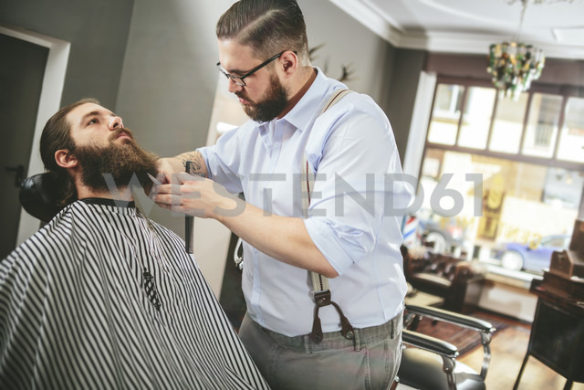 Barber cutting beard of a customer - MADF000346