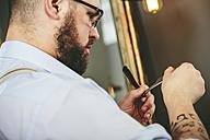 Barber checking blade of straight razor - MADF000347