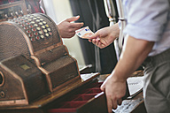 Customer paying in barber shop with antique till - MADF000356