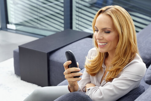 Portrait of smiling young woman sitting on couch dialing a number on cordless phone - CHAF000276