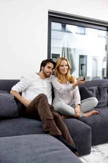 Couple sitting together on couch watching TV show - CHAF000281