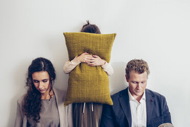 Couple having relationship conflict with their daughter hiding her face behind cushion - CHAF000324