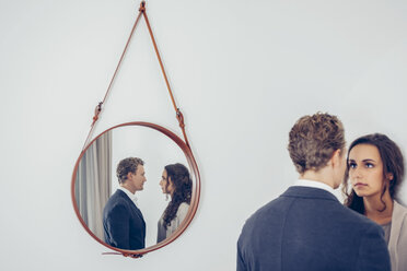 Reflection of couple in a mirror hanging on wall - CHAF000327