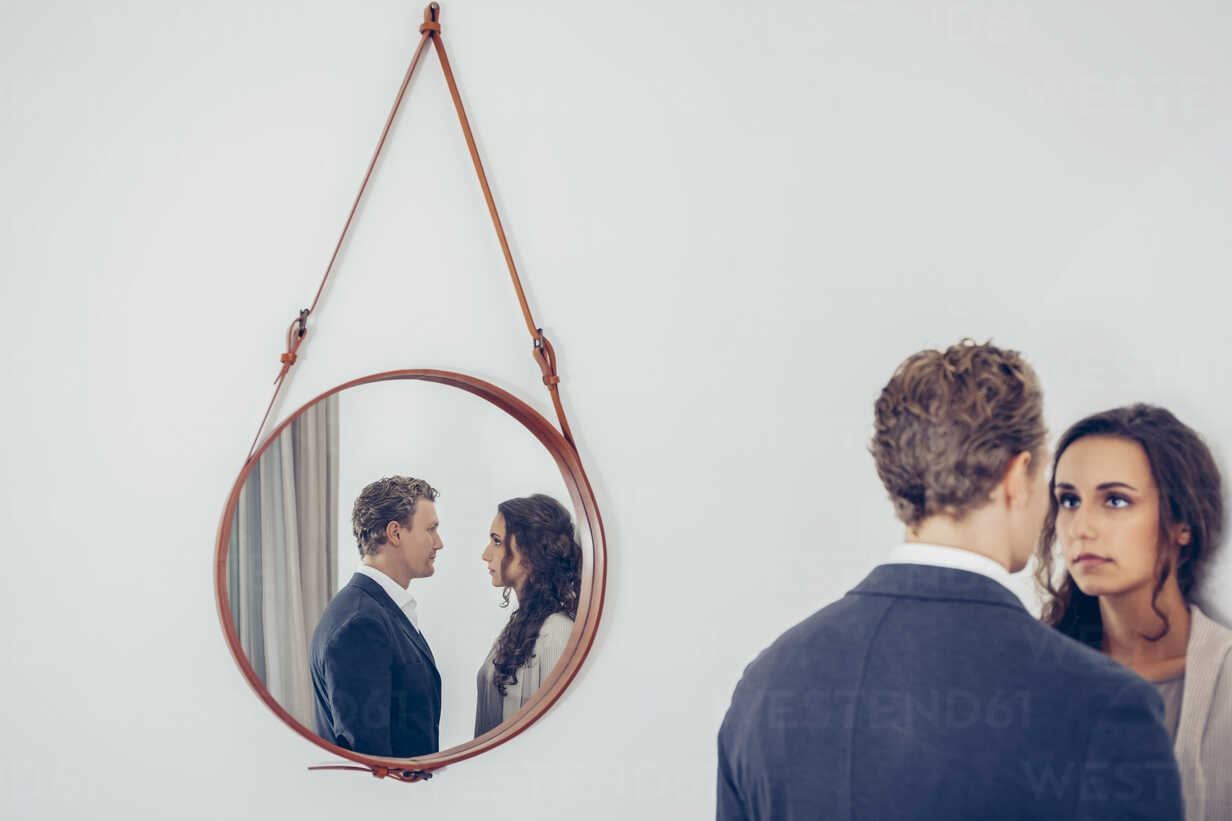 Reflection of couple in a mirror hanging on wall - CHAF000327 - Chris Adams/Westend61