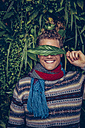 Smiling young man covering his eyes with a leaf - CHAF000328