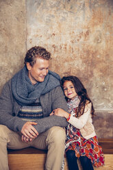 Smiling father and daughter sitting on wooden bench - CHAF000337