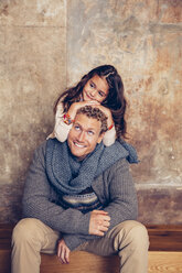 Smiling father sitting on wooden bench looking at daughter - CHAF000339