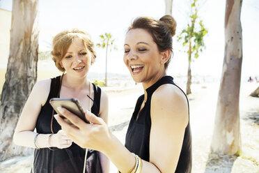 Spain, Majorca, Alcudia, two women looking at smartphone - GDF000785