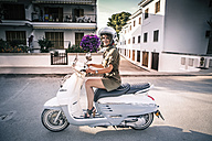 Spain, Majorca, Alcudia, woman on motor scooter - GDF000787