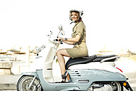 Spain, Majorca, Alcudia, woman on motor scooter - GDF000788