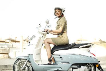 Spain, Majorca, Alcudia, woman on motor scooter - GDF000788
