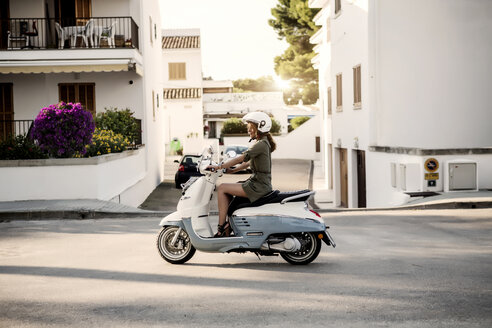 Spain, Majorca, Alcudia, woman on motor scooter - GDF000791