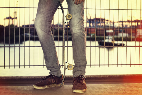 Germany, Hamburg, legs of a teenage boy with skateboard leaning against a fence - MEMF000808