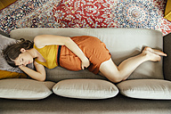 Pregnant woman taking a nap on her couch at home - MFF001789