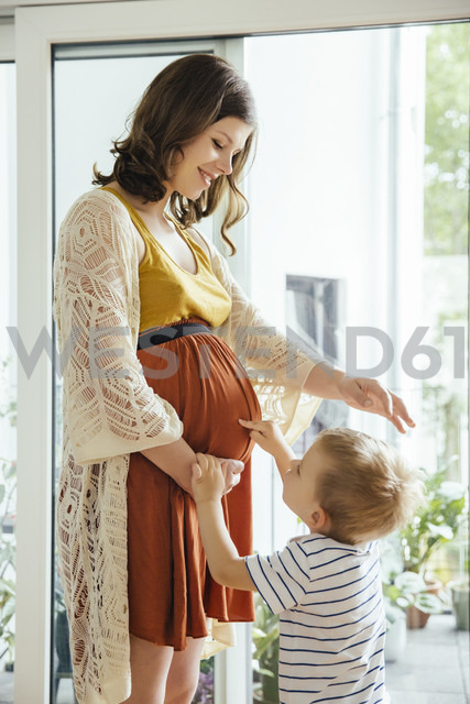 Little boy pointing at belly of his pregnant mother at home - MFF001797 - Mareen Fischinger/Westend61