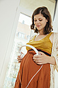 Pregnant woman holding headphones up to her baby belly at home - MFF001802