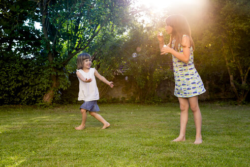 Two sisters playing with soap bubbles in a garden - LVF003615