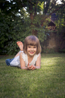 Smiling little girl lying on the meadow in the garden - LVF003616