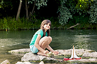 Girl playing with wooden toy boat at a river - LVF003624
