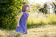 Little girl standing in hay field with closed eyes - LVF003630