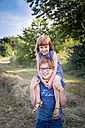 Portrait of boy carring his little sister on shoulders - LVF003633