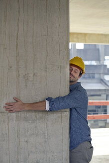 Man with hard hat embracing concrete pillar on construction site - FMKF001583