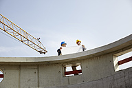 Two men on construction site discussing construction plan - FMKF001587