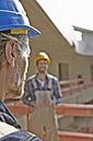 Two men with hard hats on construction site - FMKF001590