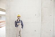 Man with hard hat on construction site at concrete wall - FMKF001601