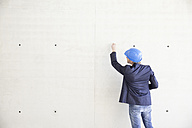 Man with hard hat on construction site drawing on concrete wall - FMKF001603