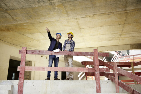 Construction worker and architect talking on construction site - FMKF001607