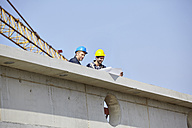 Two men on construction site looking at construction plan - FMKF001725