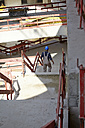 Man with hard hat on construction site walking downstairs - FMKF001727