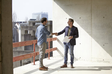 Two men on construction site shaking hands - FMKF001729
