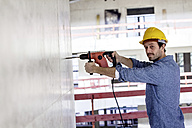 Man with hard hat on construction site using drill - FMKF001662