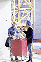 Two men on construction site having coffee break - FMKF001665